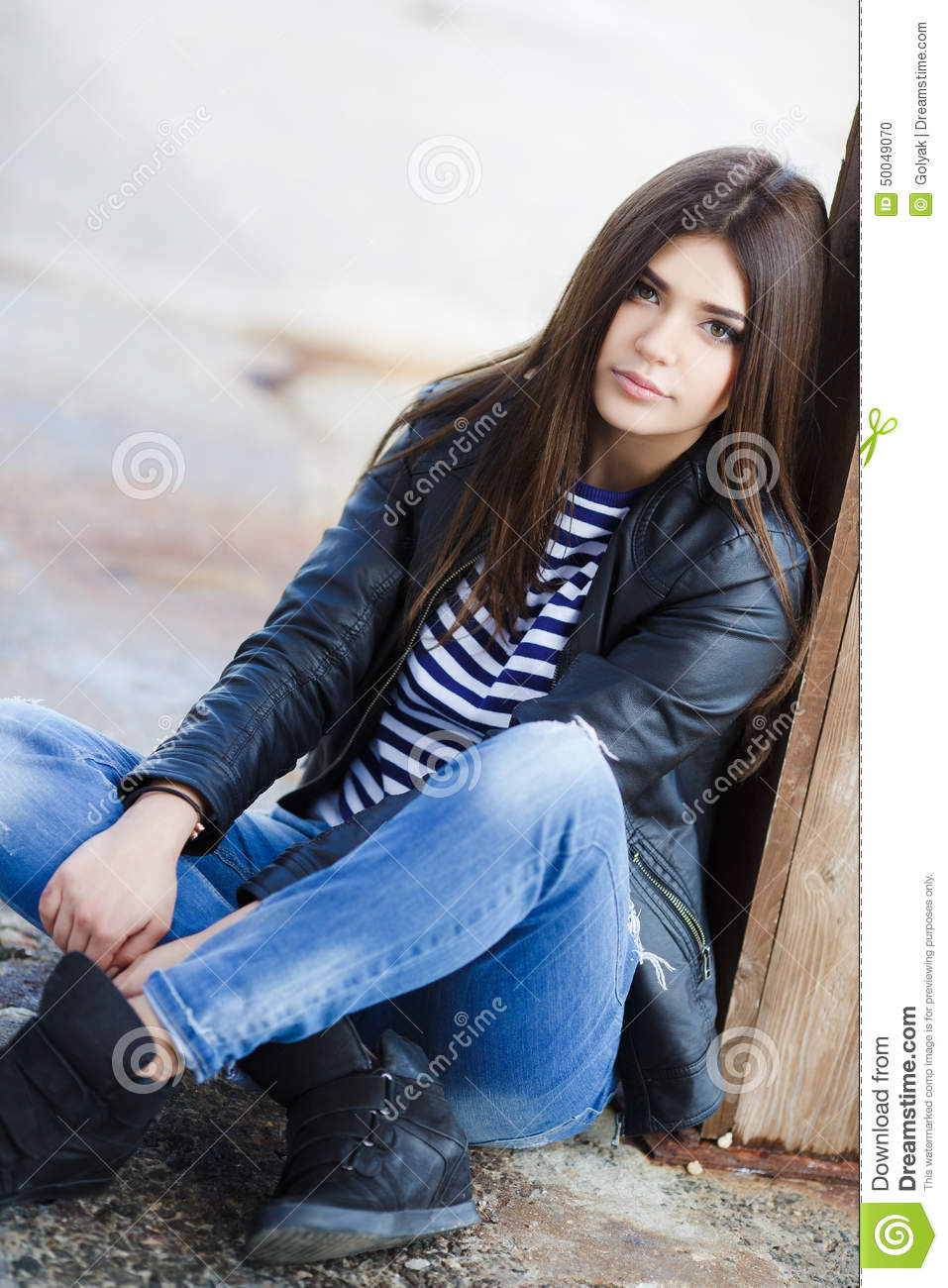 portrait of a young woman sitting on the sidewalk  stock