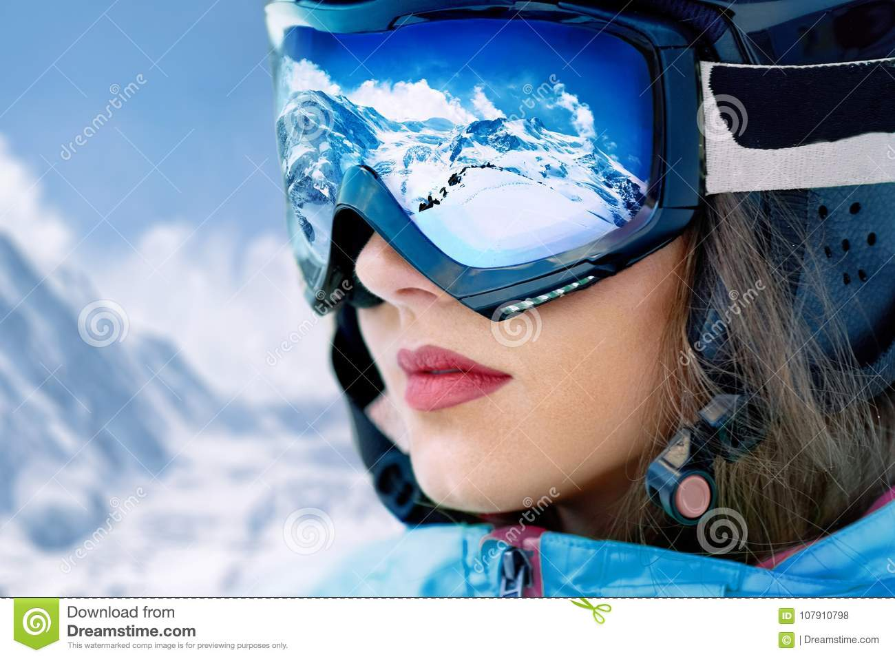 Portrait of young woman at the ski resort on the background of mountains and blue sky.A mountain range reflected in the ski mask.