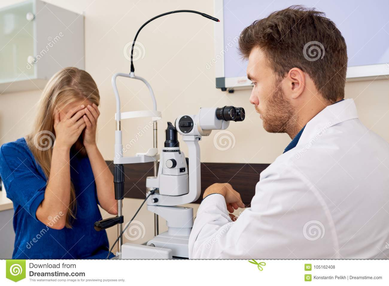 0c164473ba68 Portrait of young women covering tired eyes sitting at slit lamp during  sight testing in optometrist office