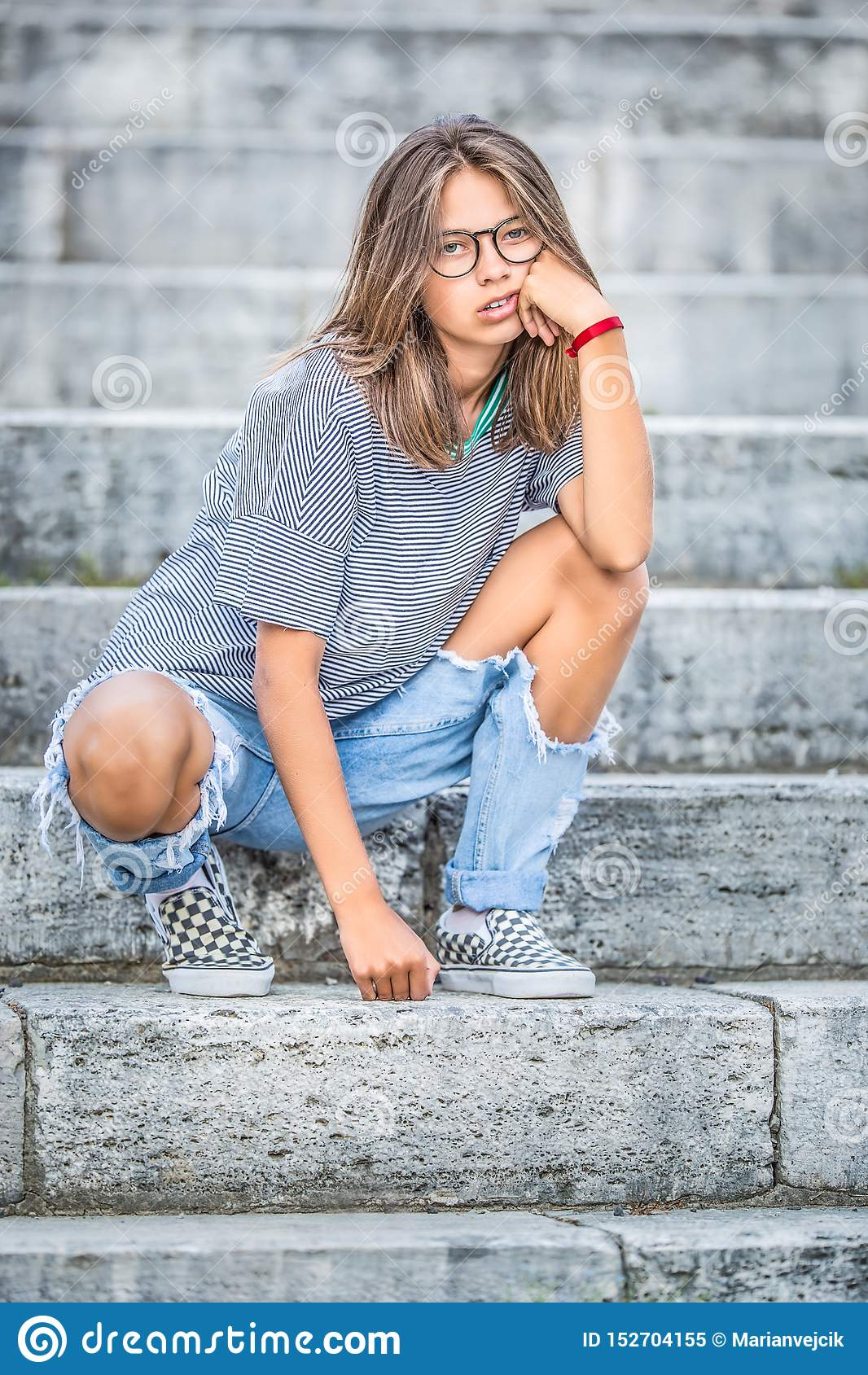 Portraito of young girl in a free modern outfit from jeans with holes