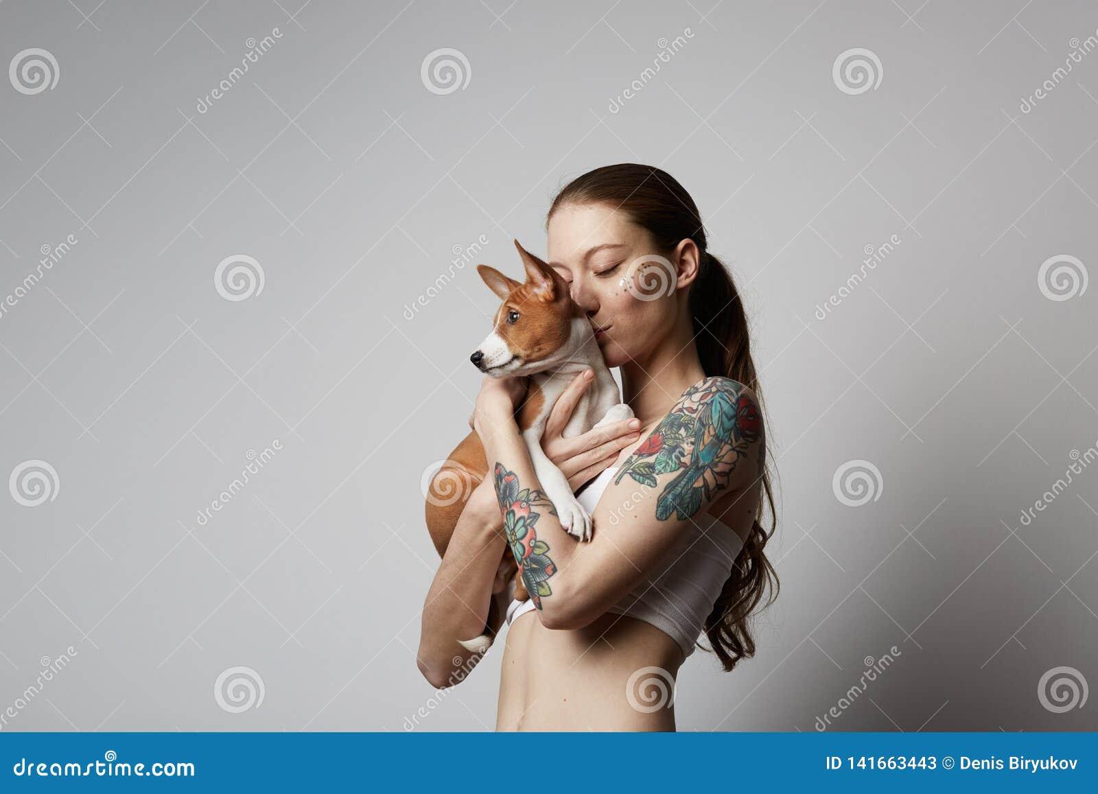 Portret śliczny tatuujący młodej kobiety całowanie i przytulenie jej mały szczeniaka basenji pies Miłość między psem i właściciel