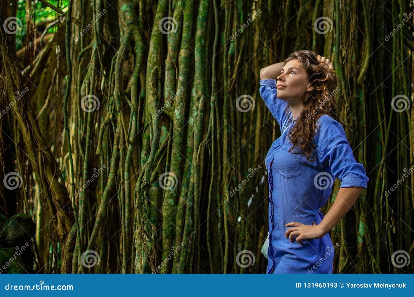 Portret ładna młoda kobieta bierze obrazek w dżungli z lians Dziewczyna stoi bezczynnie drzewa obok ona _