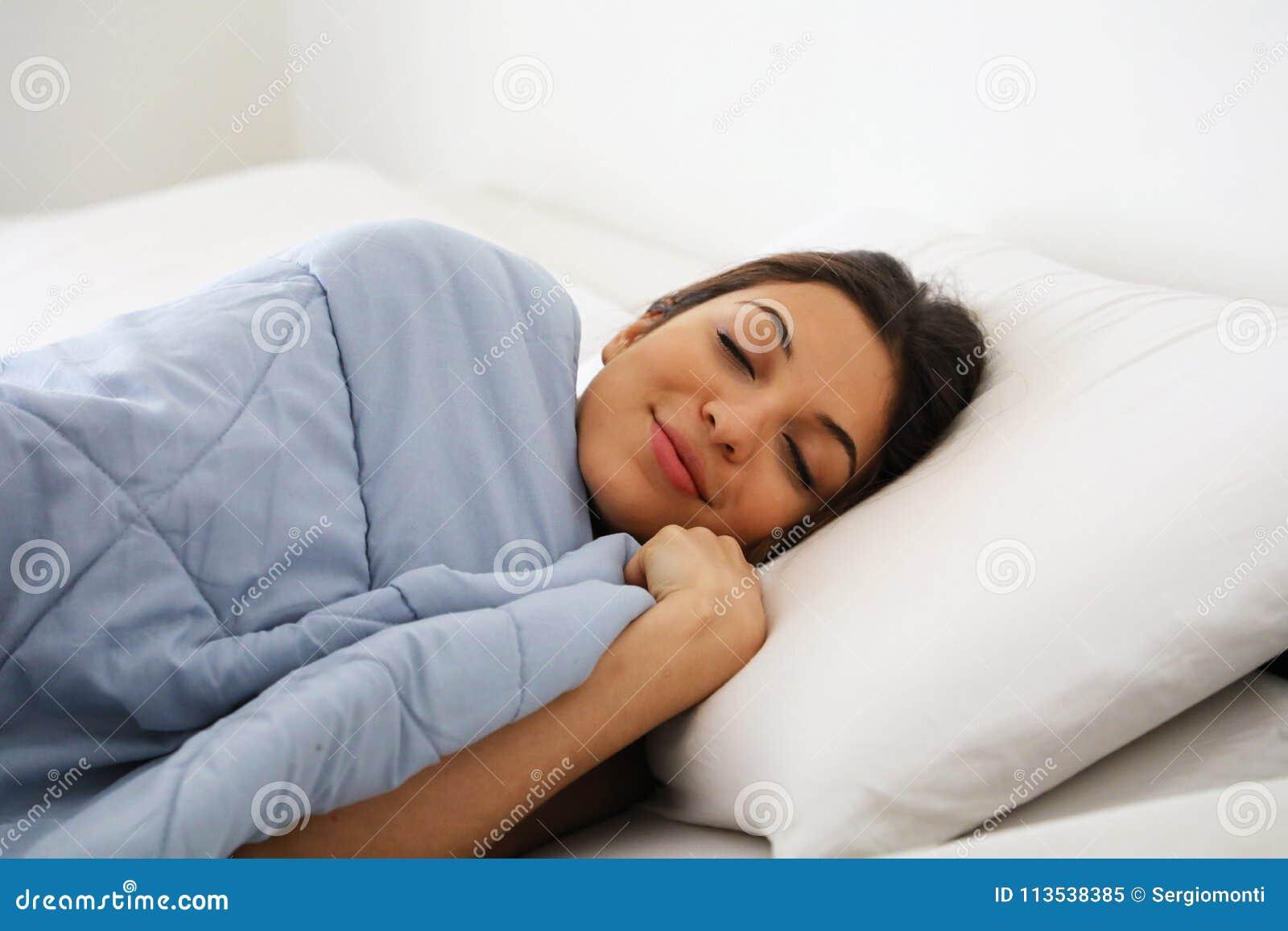 Portret ładna młoda kobieta pod koc w nowożytnym mieszkaniu w ranku Utrzymuje oczy zamyka i patrzeje zadowoloną
