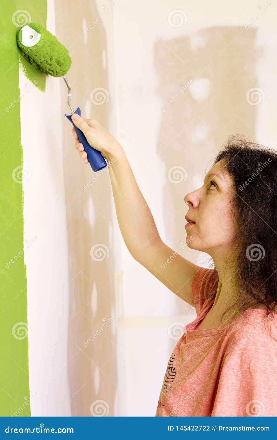 Portret ładna młoda kobieta w różowej koszulce ostrożnie maluje zieloną wewnętrzną ścianę z rolownikiem w nowym domu