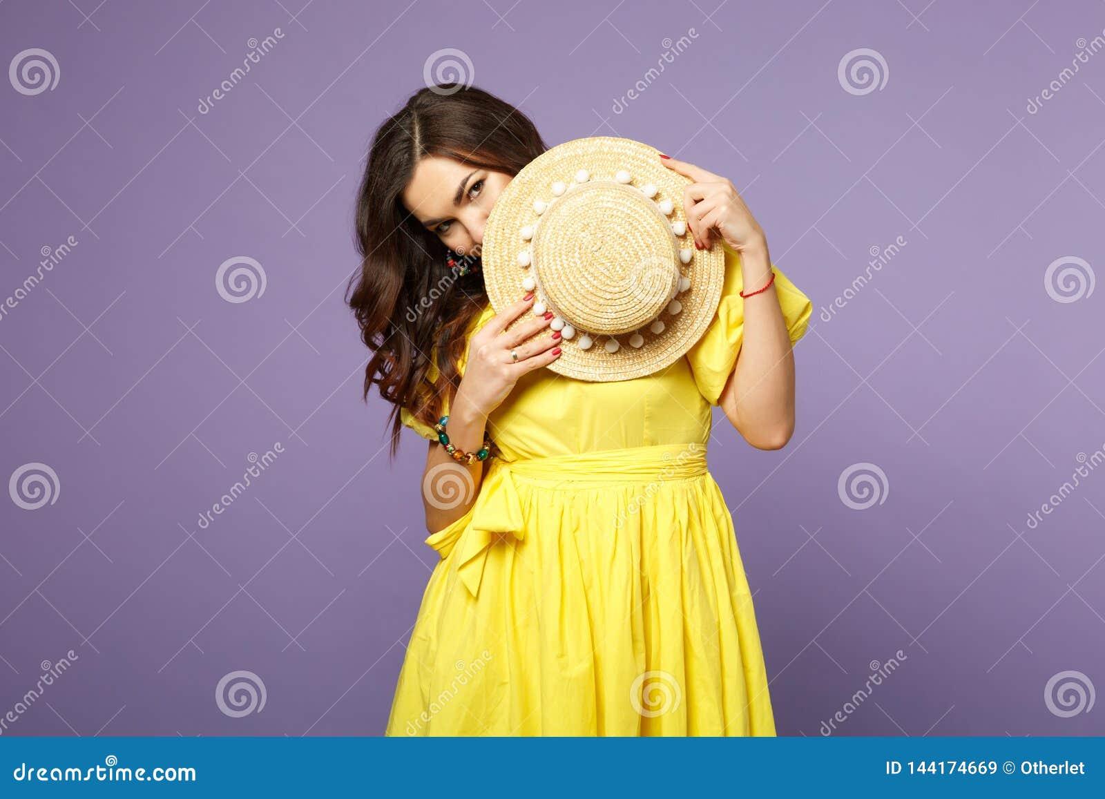 Portret ładna zmieszana młoda kobieta w kolor żółty sukni nakrycia twarzy z lato kapeluszem na pastelowym fiołku