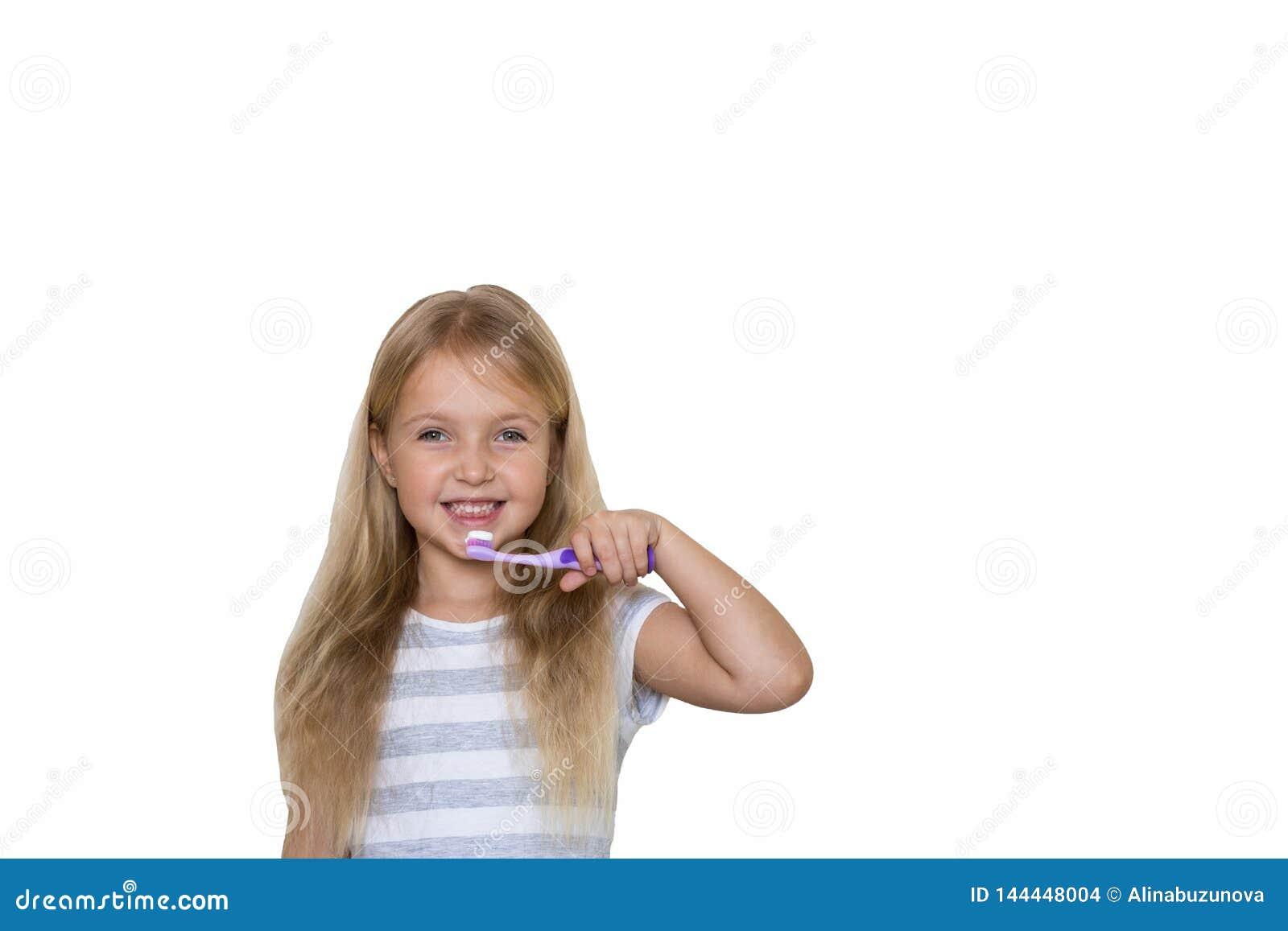 Portret śliczna mała dziewczynka z blondynka włosy który odizolowywał na białym tle czyści ząb z muśnięciem i pastą do zębów