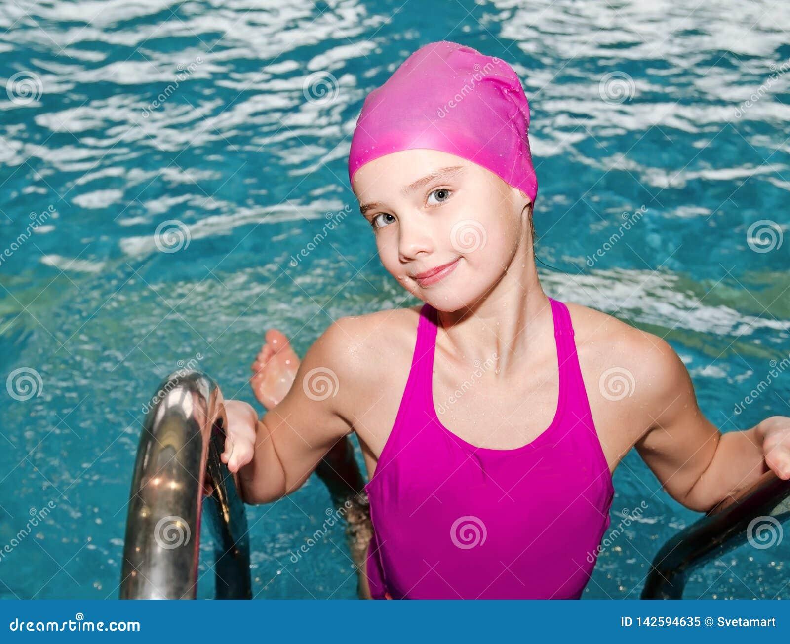 Portret śliczna uśmiechnięta małej dziewczynki dziecka pływaczka w różowym pływackim kostiumu i nakrętce w basenie