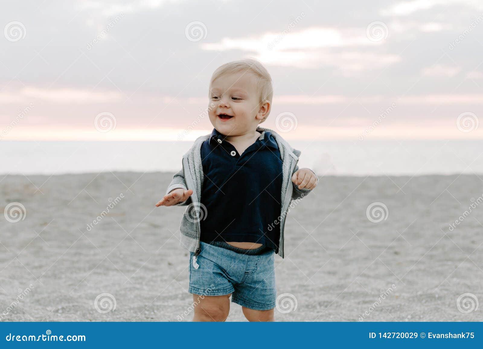 Portret Śliczny Mały chłopiec dziecko Bawić się i Bada w piasku przy plażą Podczas zmierzchu Outside na wakacje w Hoodie