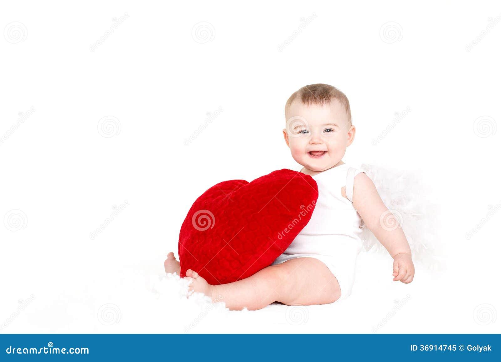 Portret Śliczny uroczy mały valentine anioł z czerwonym miękkim sercem odizolowywającym na białym tle