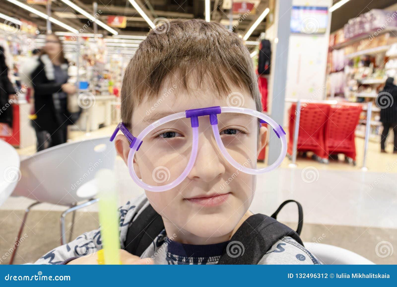 Portret śmieszna śliczna chłopiec jest ubranym dziwacznych szkła robić fluorescencyjne neonowe tubki, centrum handlowe