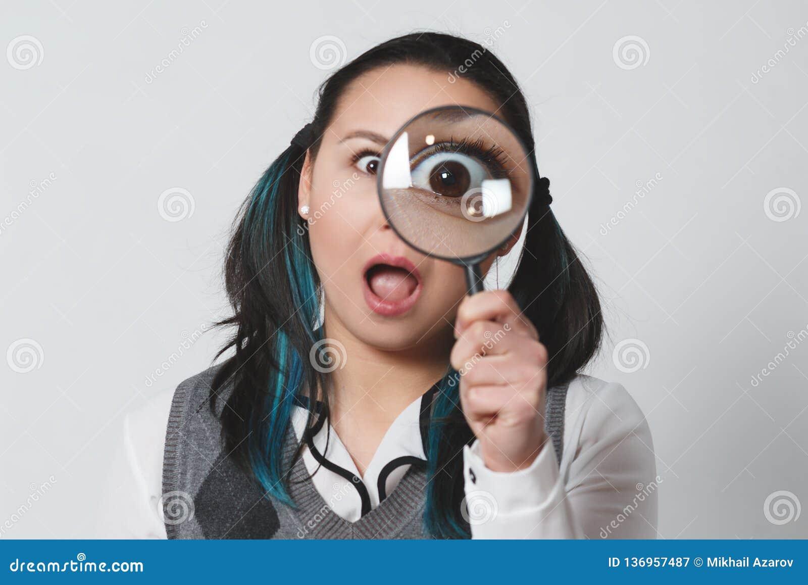 Portret śmieszna młoda kobieta patrzeje kamerę przez powiększać - szkło na szarym tle