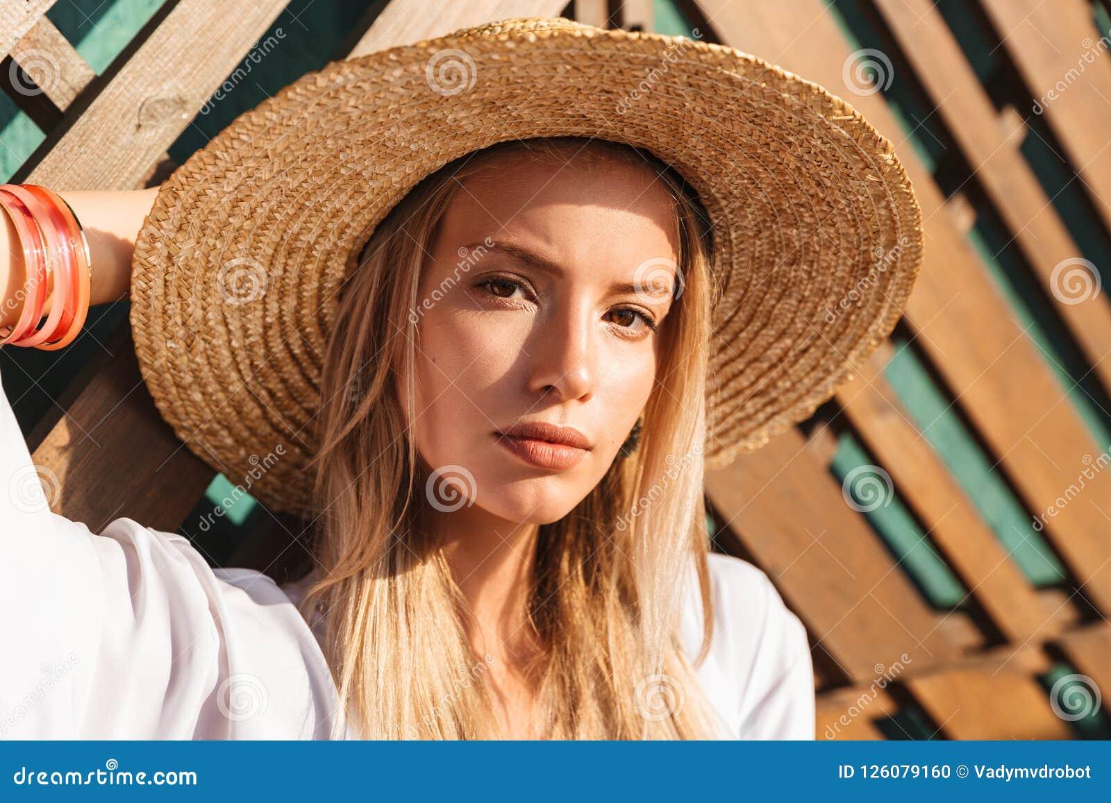 Portret atrakcyjna młoda blond kobieta 20s w słomianym kapeluszu i sw