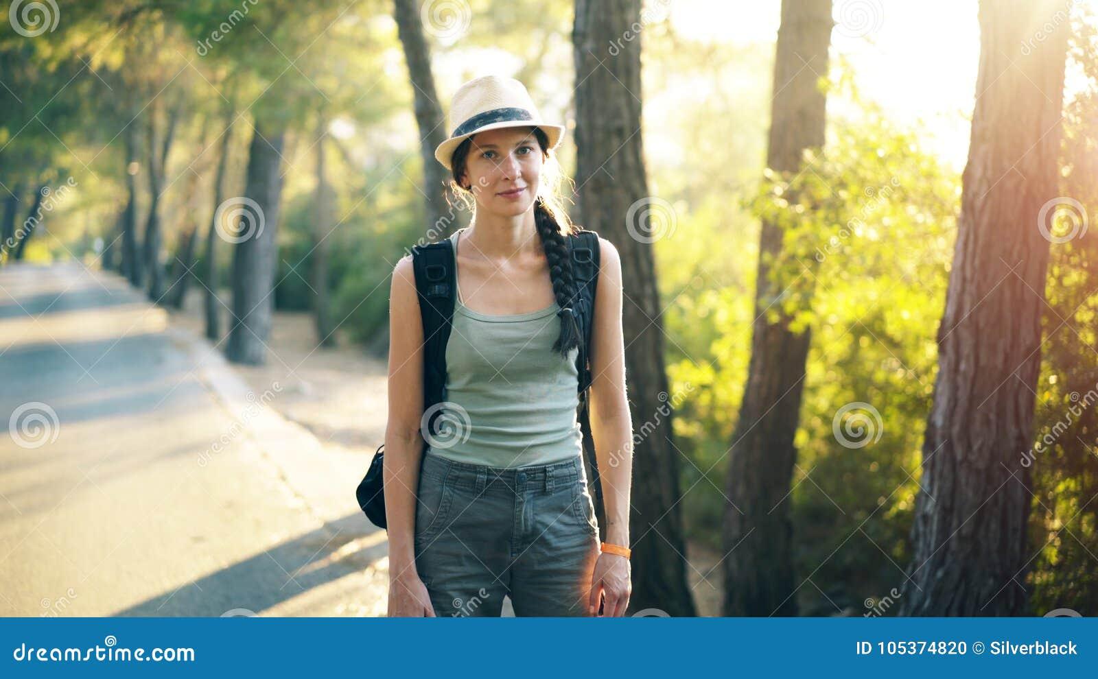 Portret Atrakcyjna turystyczna dziewczyna uśmiechnięta i patrzeje w kamerę podczas gdy chodzący pięknego las i wycieczkujący