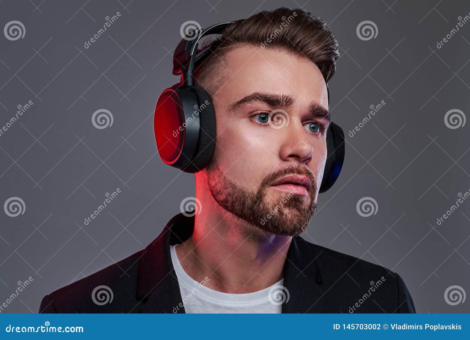 Portret atrakcyjny młody człowiek który jest słuchającym muzyką w bezprzewodowych hełmofonach