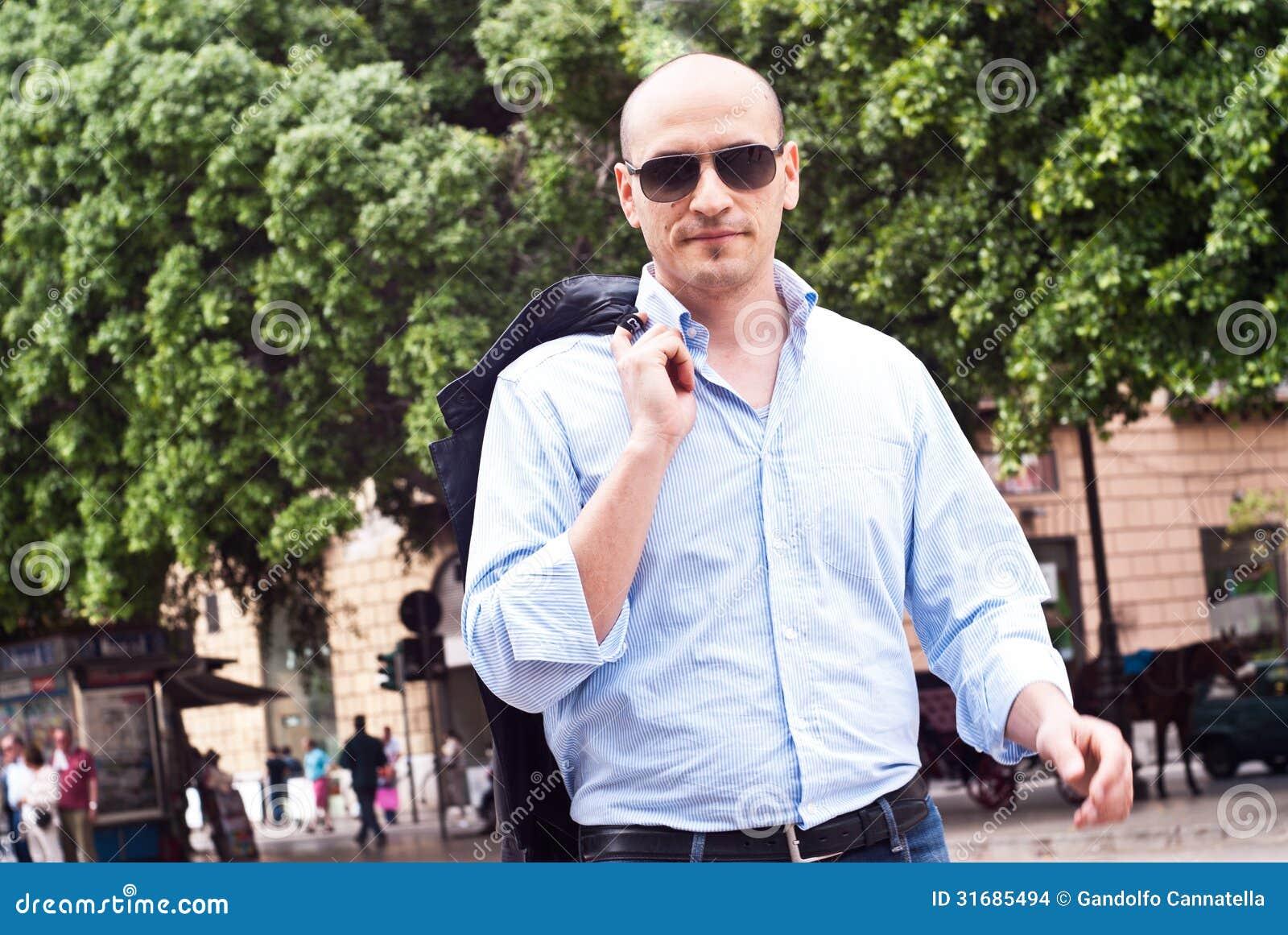 Portret atrakcyjny wspaniały facet jest ubranym okulary przeciwsłonecznych