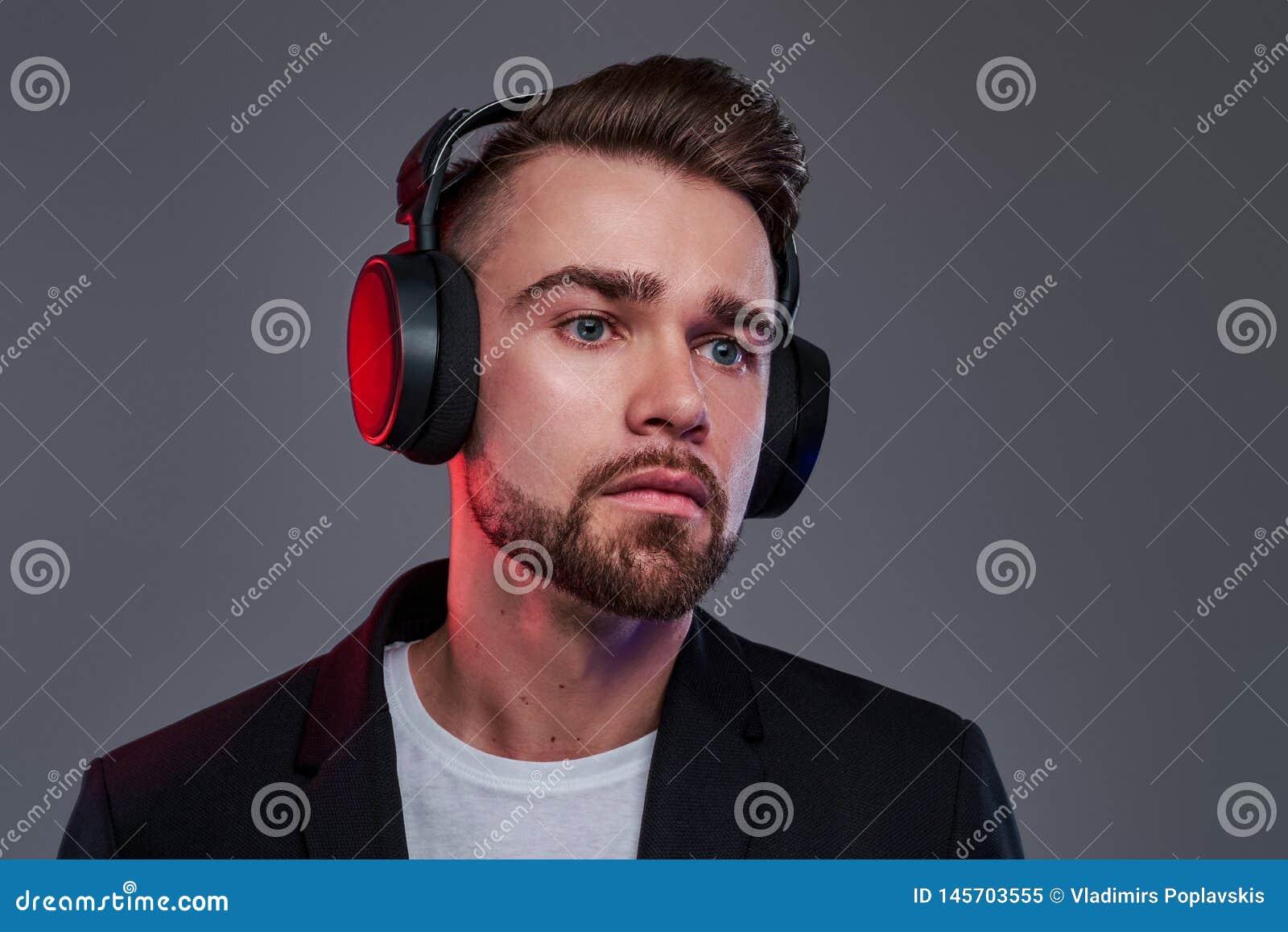 Portret atrakcyjny zadumany m??czyzna w bezprzewodowych he?mofonach
