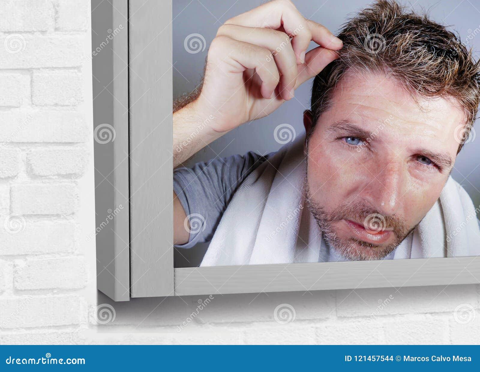 Portret atrakcyjny zmartwiony i zaniepokojony Kaukaski mężczyzna patrzeje łazienki lustra znalezienie himself z szarym włosy w ki