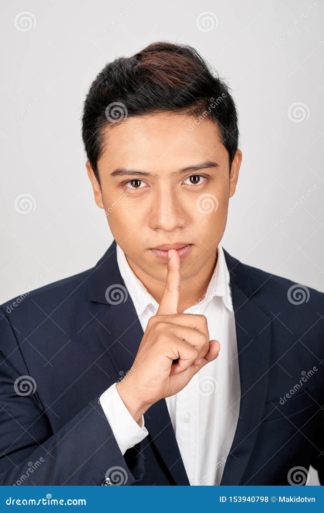 Portret Azjatycki przystojny biznesmen ubierał w kostiumu seansu ciszy gescie i patrzeć kamerę odizolowywającą nad bielem
