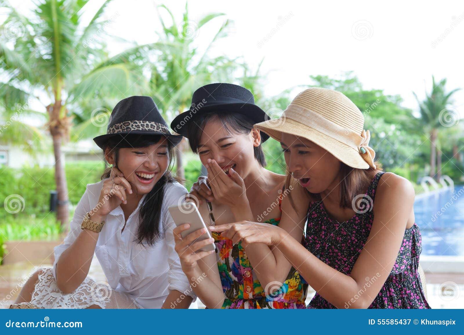 Portret azjatykcia kobieta przyjaciela grupa patrzeje telefon komórkowy i
