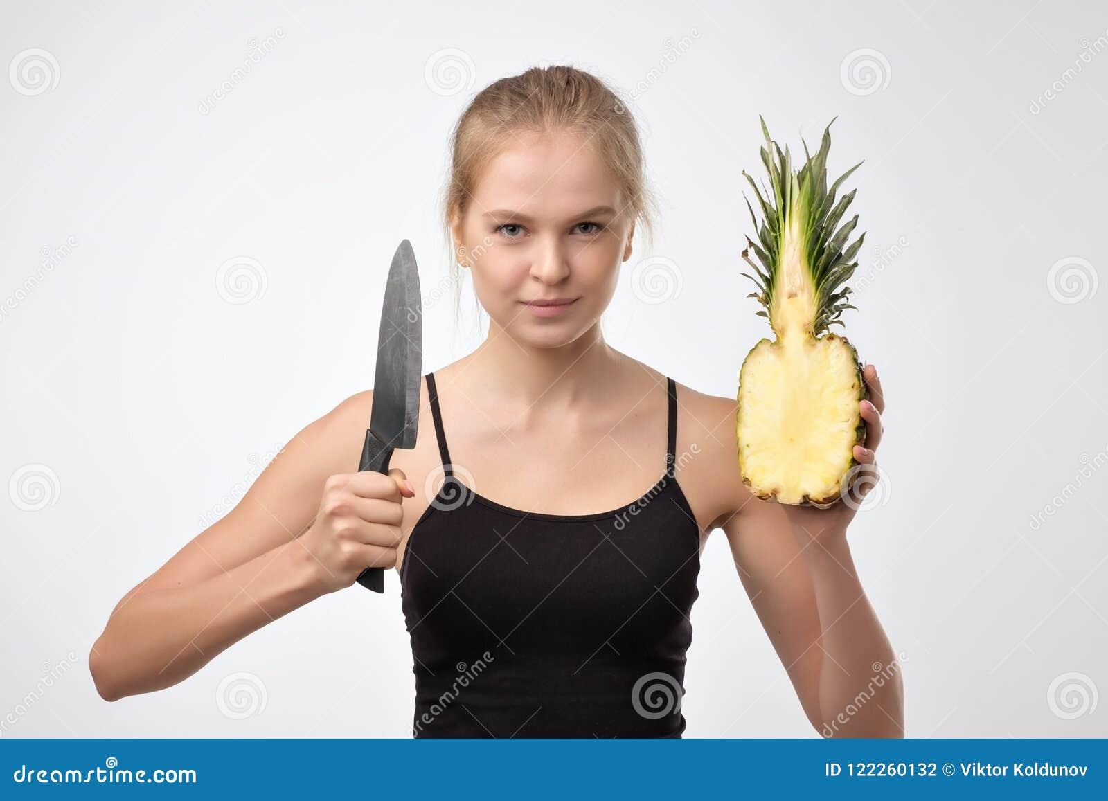 Portret blondynki kobieta która utrzymuje ananasa i noża w rękach przeciw białemu tłu