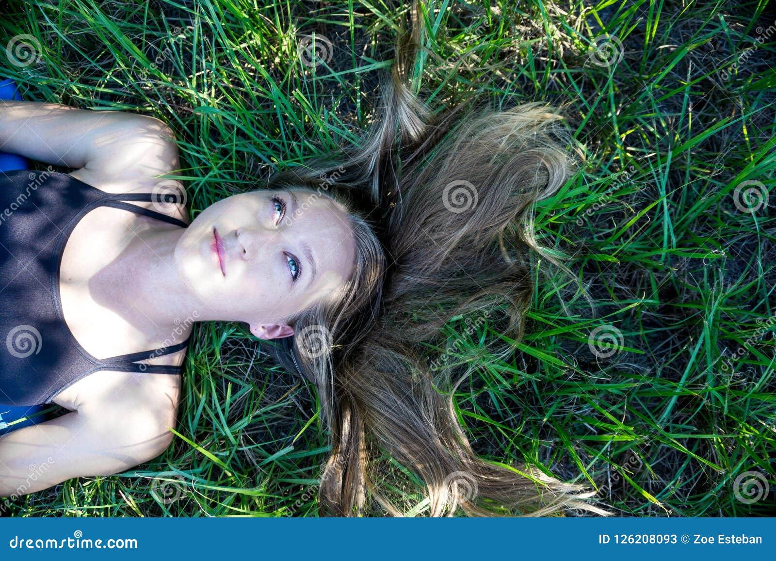Portret blondynki młoda kobieta kłaść w trawie z długie włosy i niebieskich oczu przyglądający up szczęśliwym