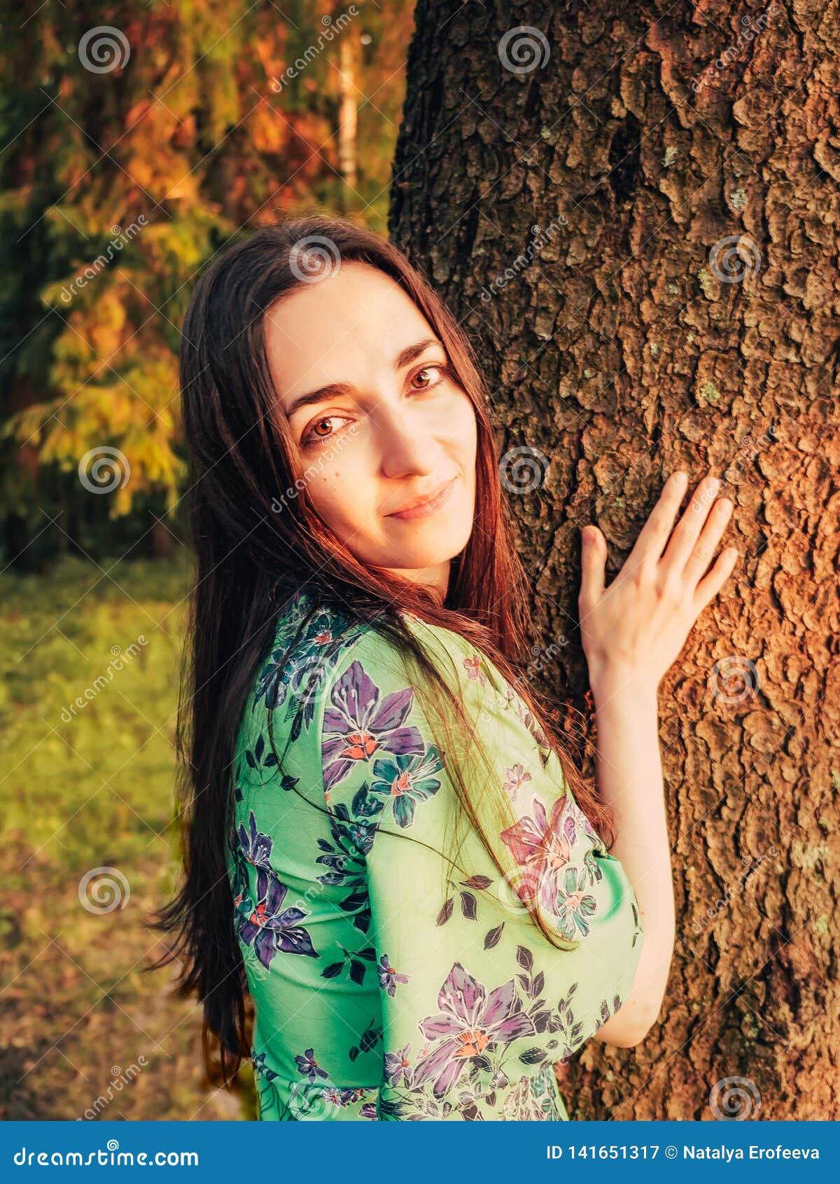 Portret brunetki piękna uśmiechnięta caucasian dziewczyna z długie włosy w lesie przy zmierzchem opierał przeciw drzewu jedność