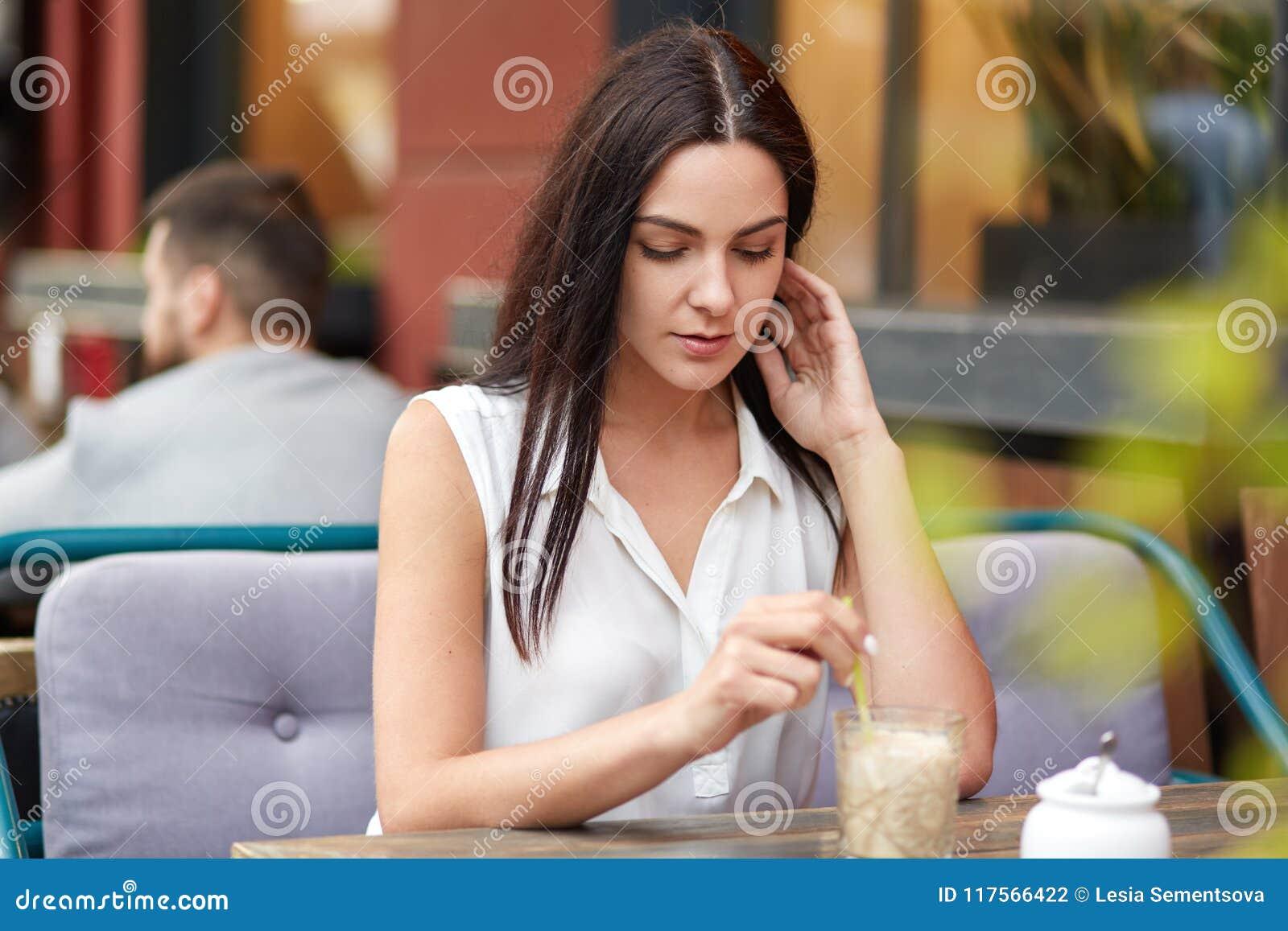 Portret brunetki poważna kobieta rozważnego wyrażenie, pije koktajl w plenerowej kawiarni, czeka partnera biznesowego, cieszy się