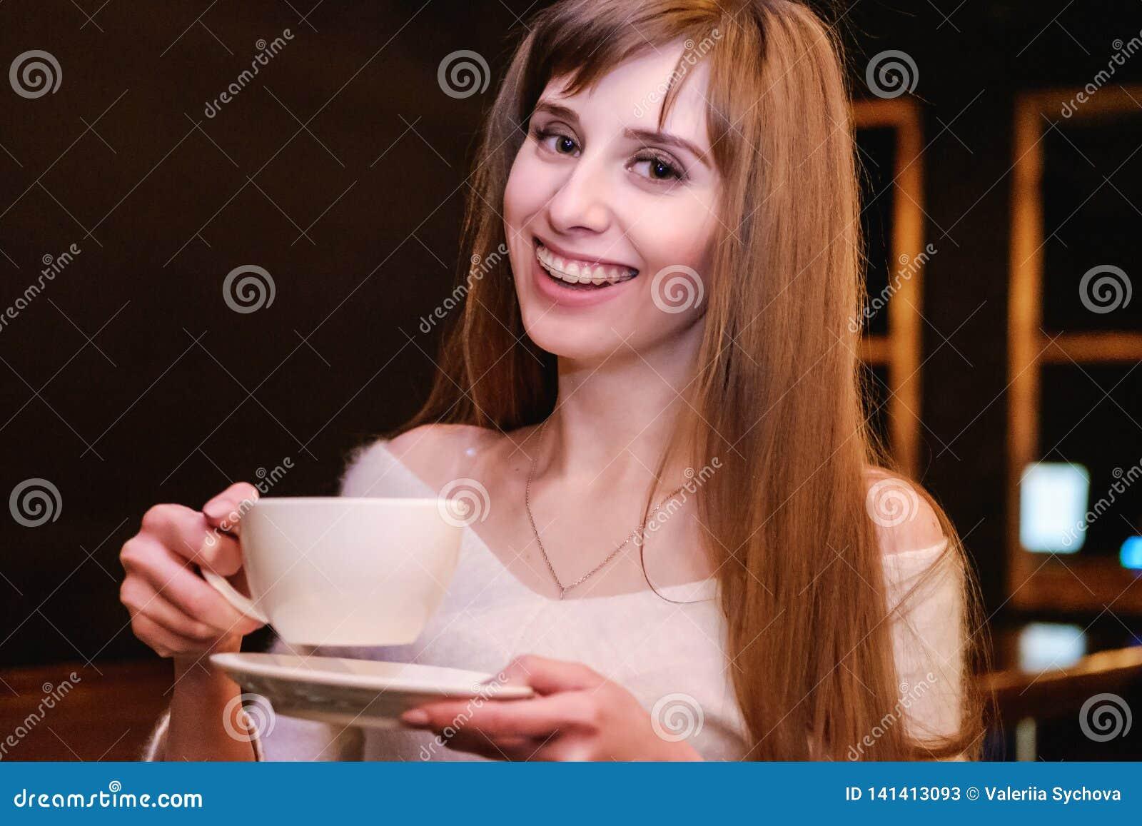 Portret długowłosa piękna dziewczyna w białym pulowerze Dziewczyny stojaki w sklepie z kawą przy drewnianym stołem i chwytami fil