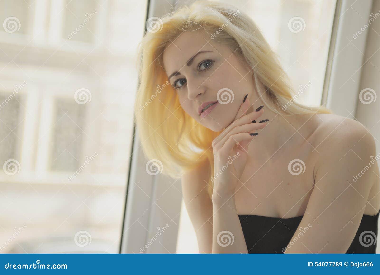 Portret dichte omhooggaand van jonge mooie blondevrouw dichtbij venster