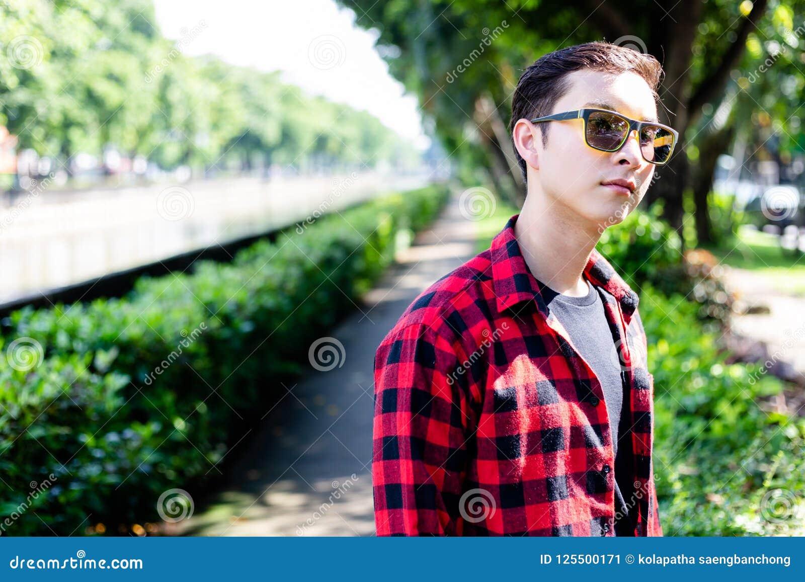 Portret die de knappe jonge mens charmeren Aantrekkelijke sungla van de kerelslijtage