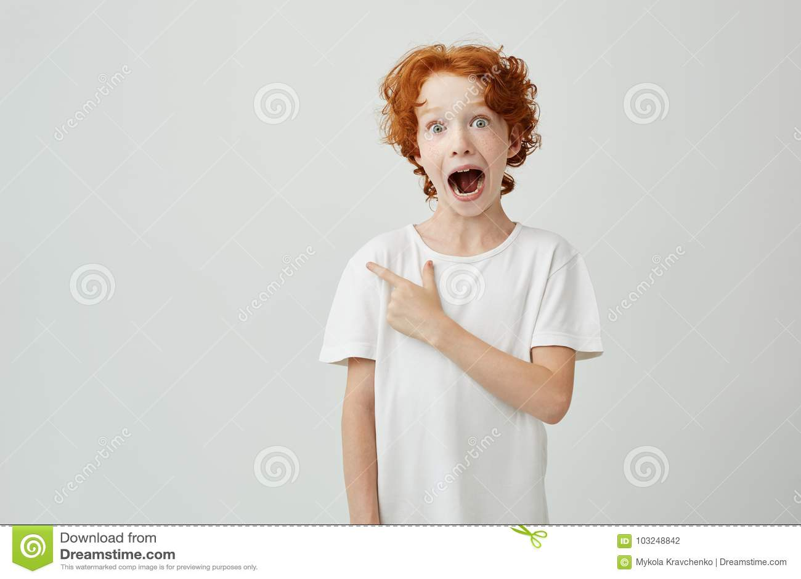 Portret die van blij gemberkind met sproeten die met geopende mond en gekke uitdrukking stellen, op vrije ruimte richten voor