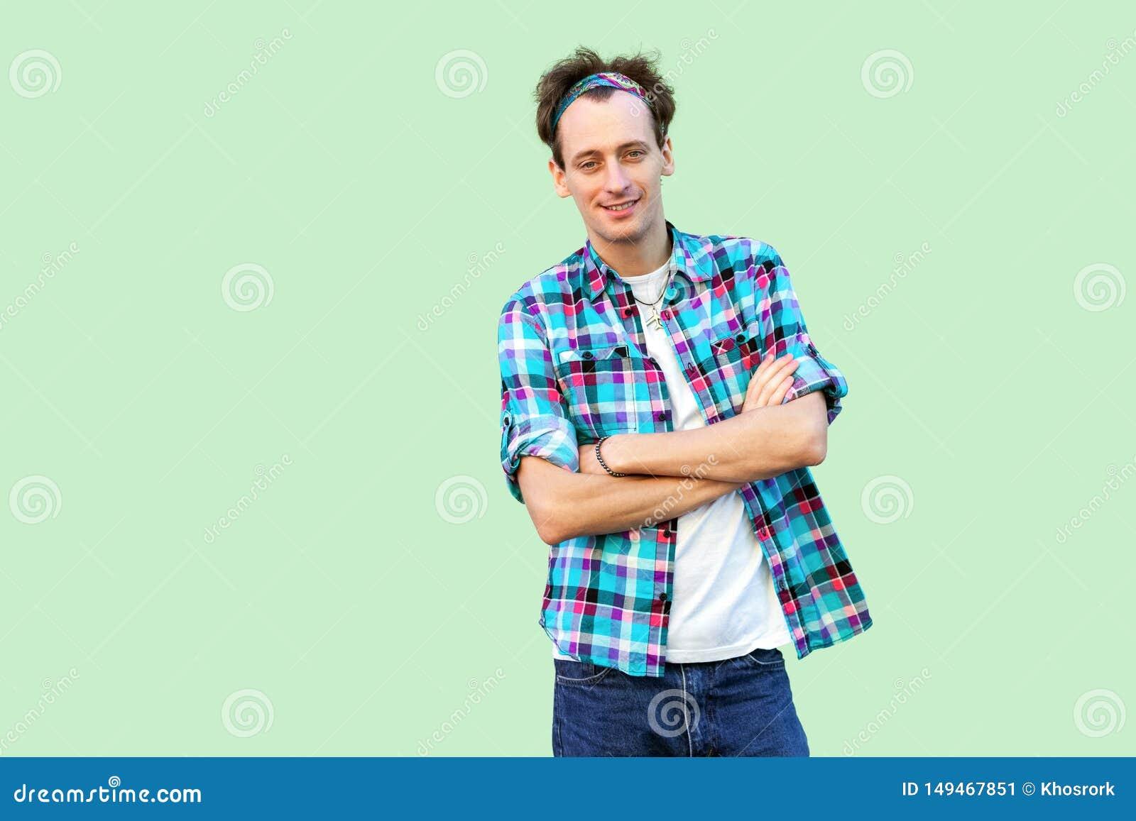 Portret die van de gelukkige tevreden jonge mens in toevallig blauw geruit overhemd en hoofdband die, camera het bekijken met cro