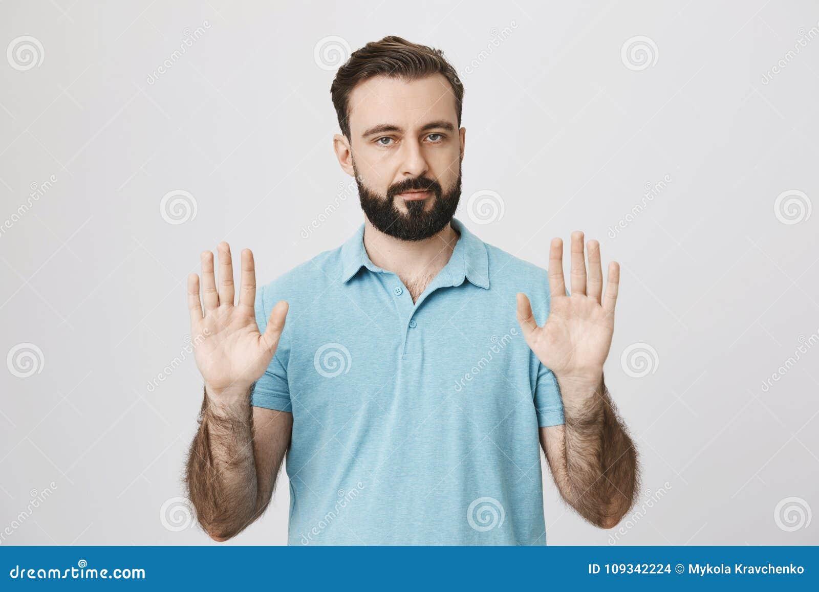 Portret die van de kalme volwassen mens met baard die zijn palmen opheffen en camera bekijken, zich over grijze achtergrond bevin