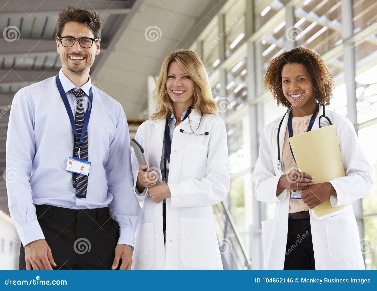 Portret die van drie mannelijke en vrouwelijke artsen, aan camera kijken