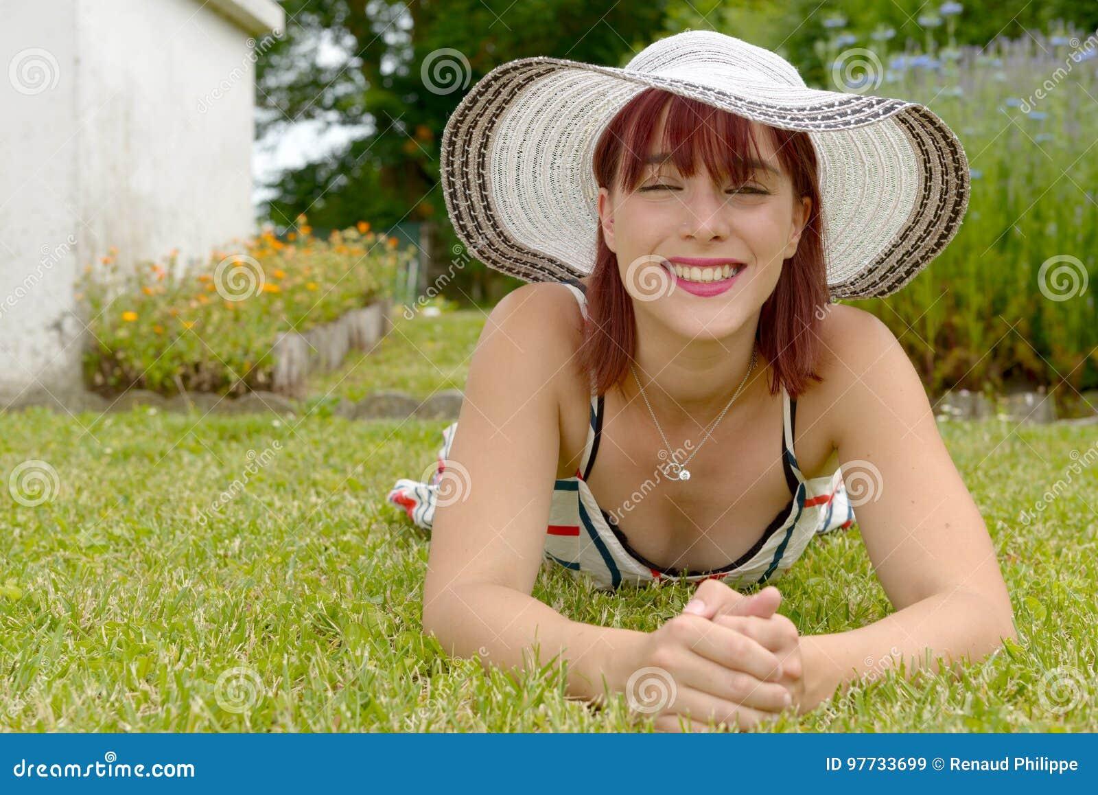 Portret die van een mooi meisje met de zomerhoed, op gras liggen