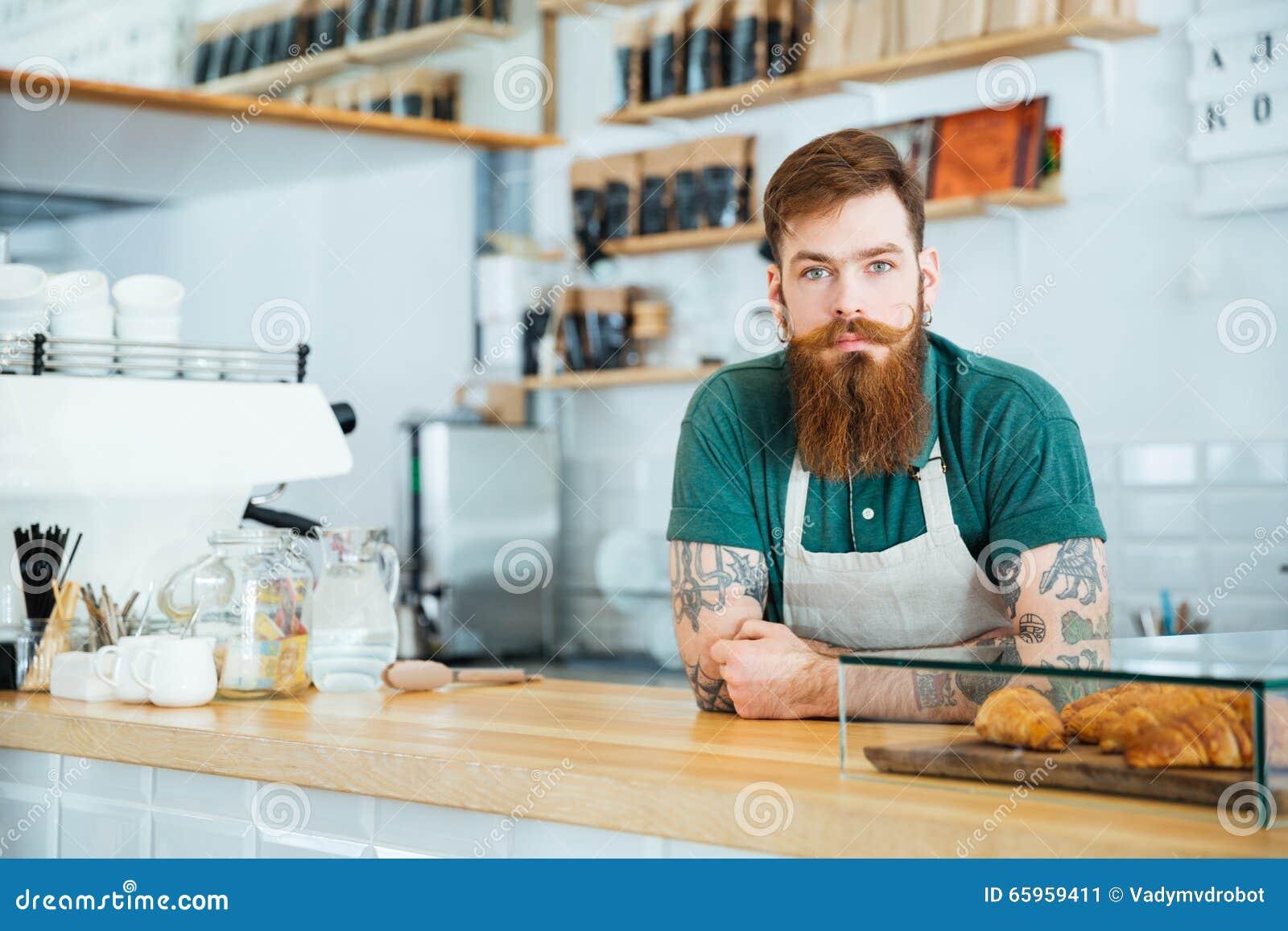 Portret die van gebaarde mannelijke barista zich in koffiewinkel bevinden