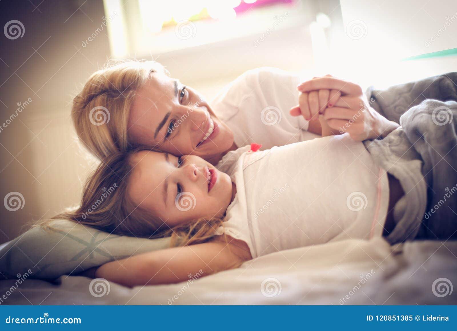 Portret die van gelukkige moeder en dochter op een bed liggen