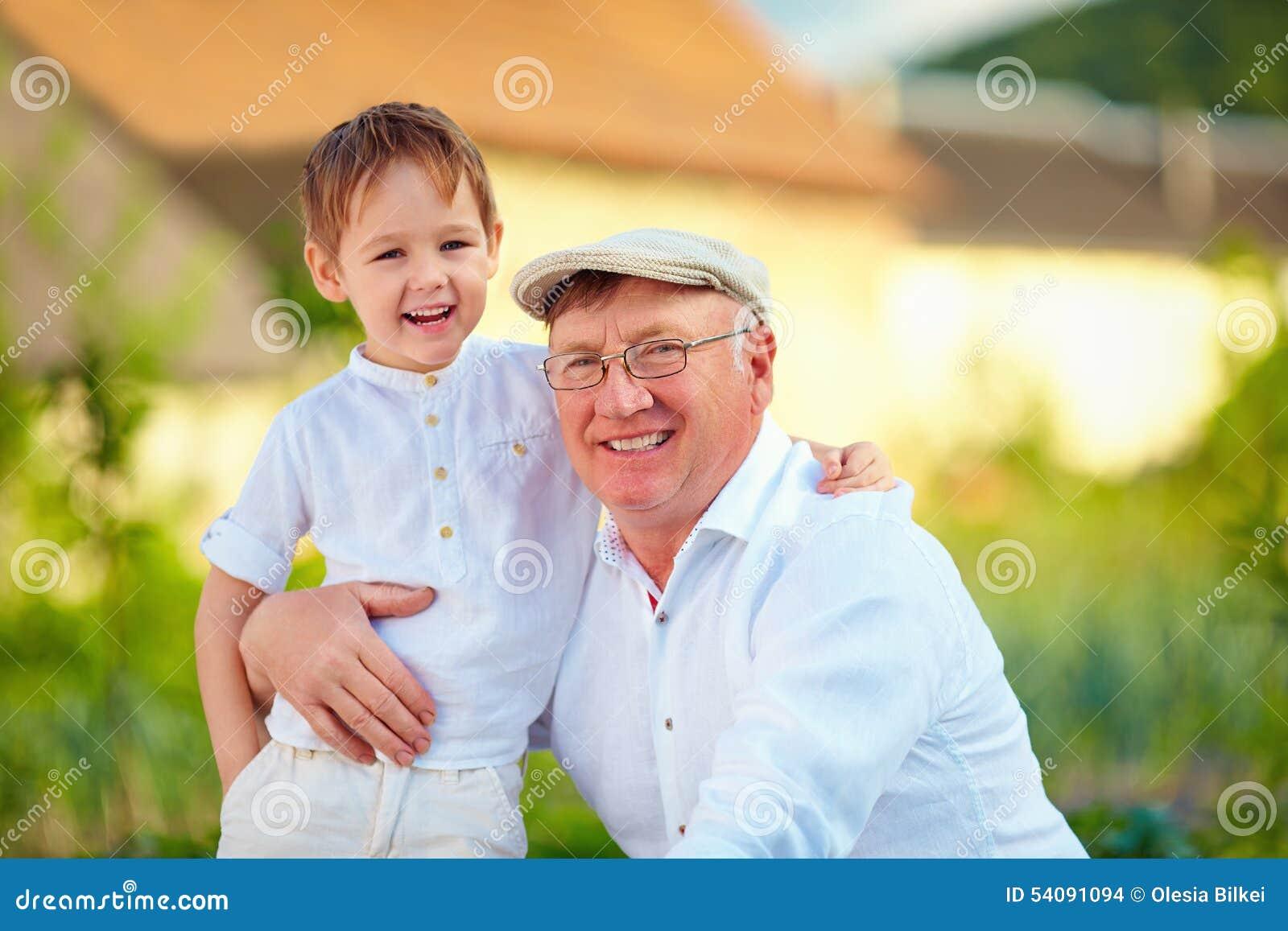 Portret die van gelukkige opa en kleinzoon in openlucht omhelzen