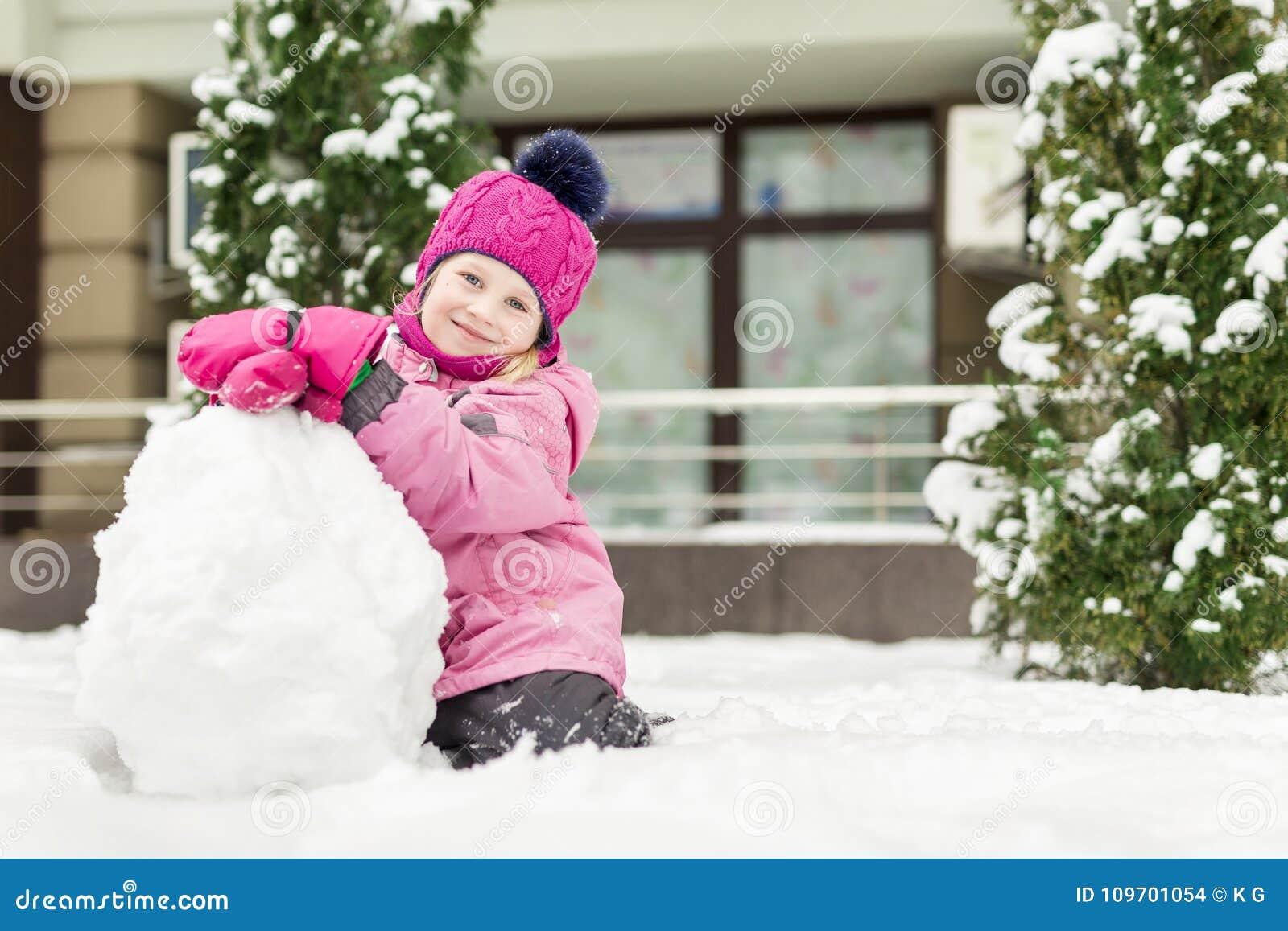 Portret die van leuk meisje smowman maken bij heldere de winterdag Het aanbiddelijke kind spelen met sneeuw in openlucht grappig