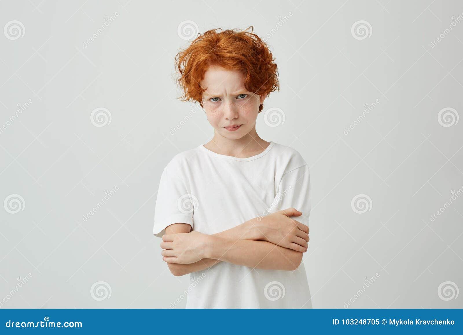 Portret die van ongelukkige rode haired jongen die met sproeten in camera met verstoorde uitdrukking, handen kruisen die zijn kij