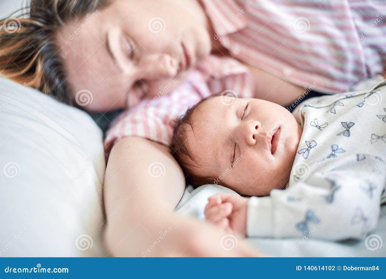 Portret die van pasgeboren baby en moederslaap op bed, samen rusten