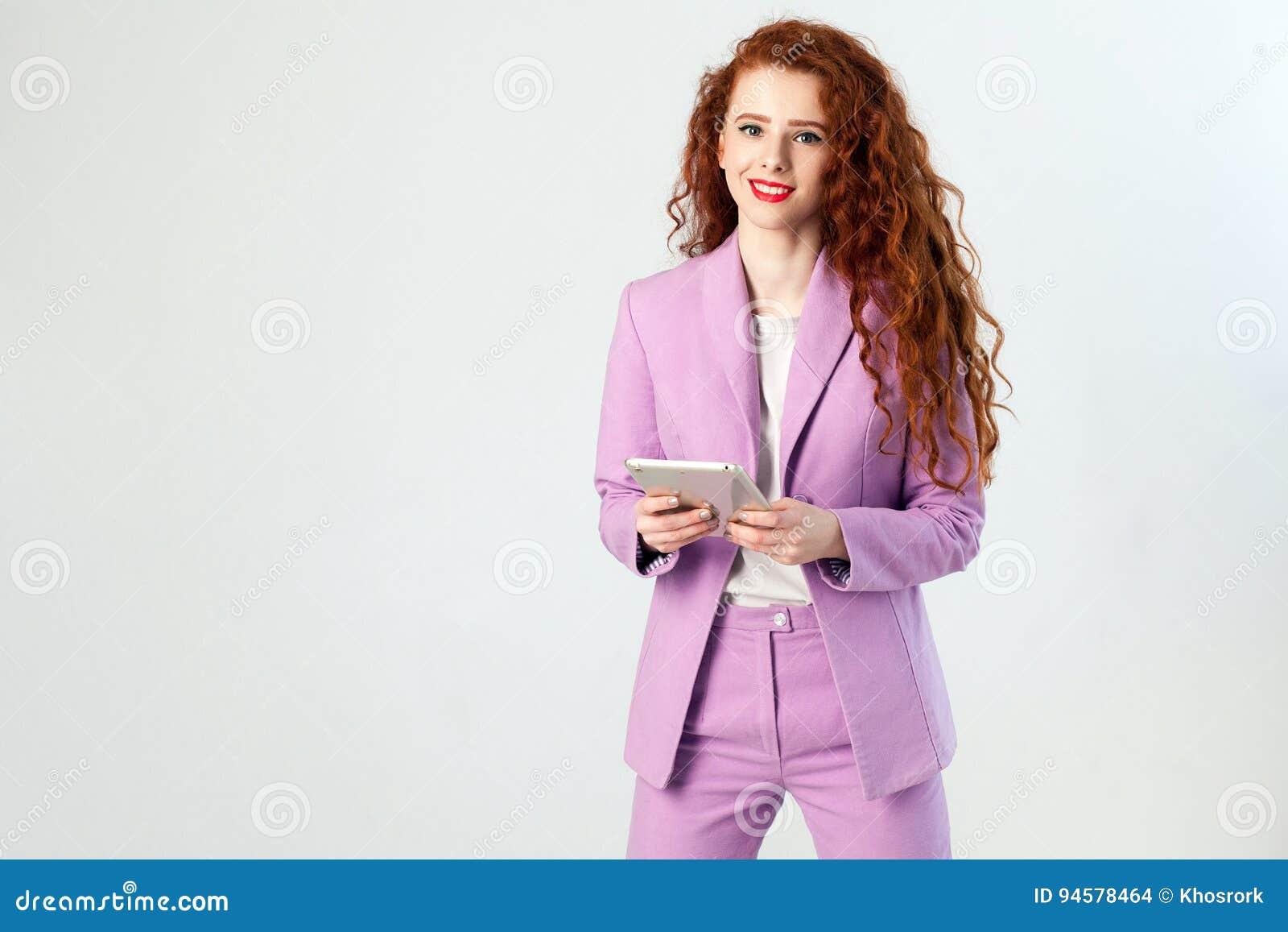 Portret die van succesvolle gelukkige mooie bedrijfsvrouw met roodbruin haar en make-up in de roze tablet van de kostuumholding,