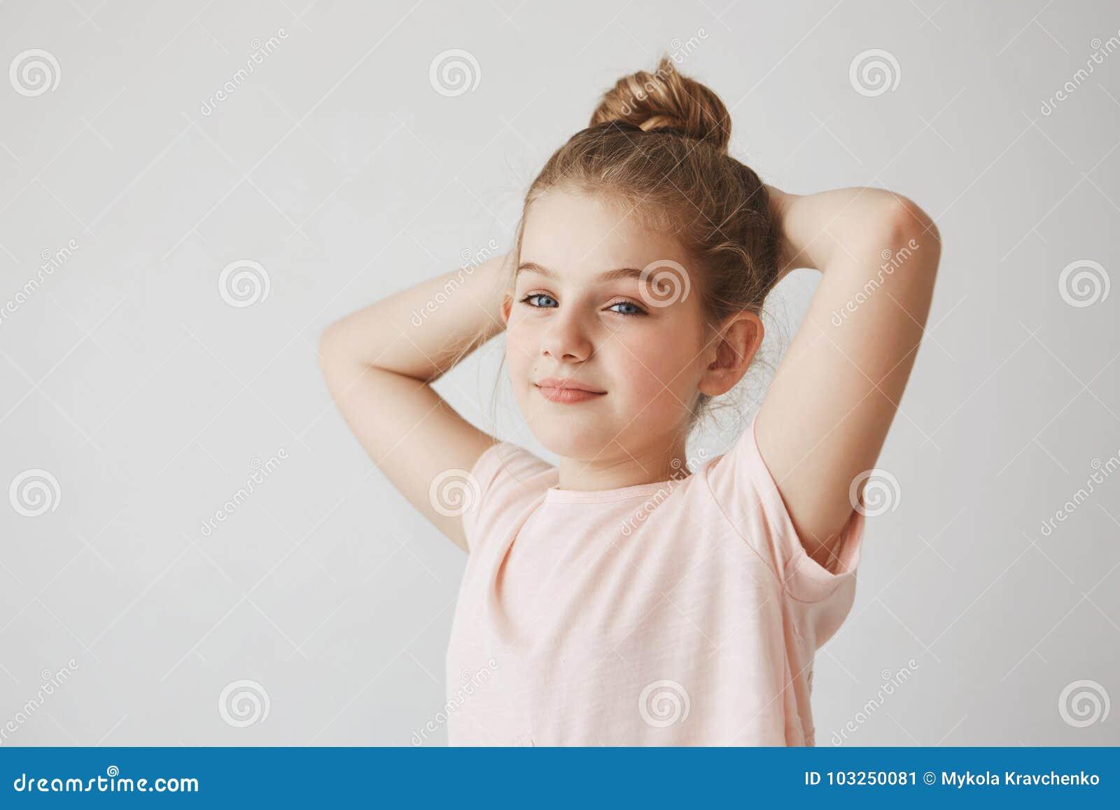 Portret die van vrolijk onbezorgd kind die met blond haar in broodjeskapsel, handen achter hoofd houden brightfully glimlachen