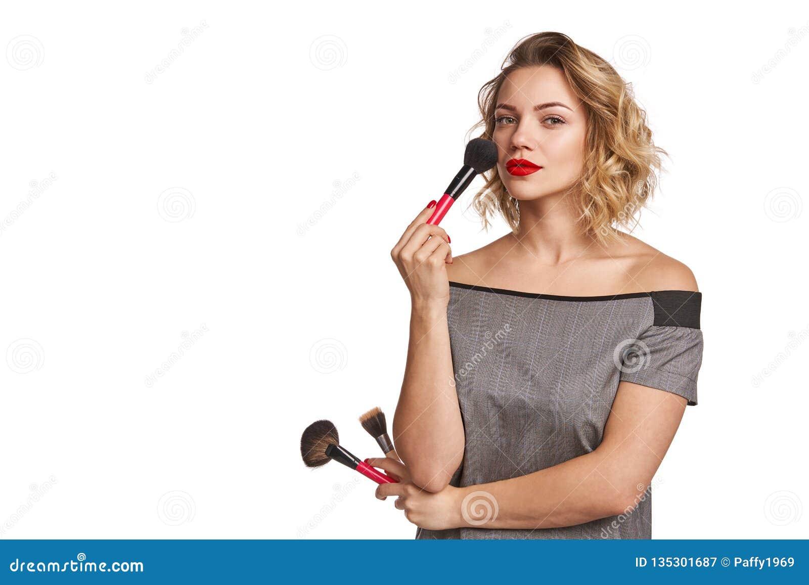 Portret die van vrouwelijke stilist zich met make-upborstels bevinden