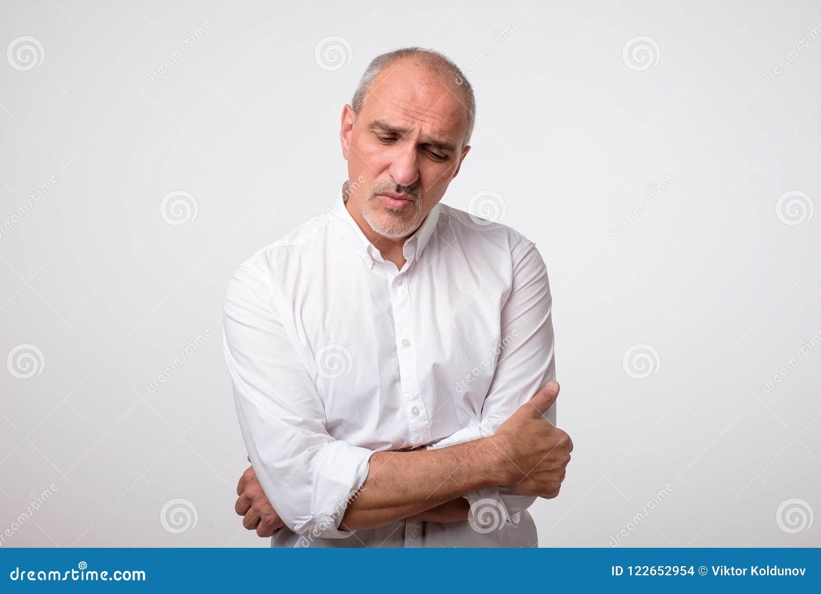 Portret dojrzały przystojny mężczyzna w białej koszula z poważnym i smutnym wyrażeniem na twarzy