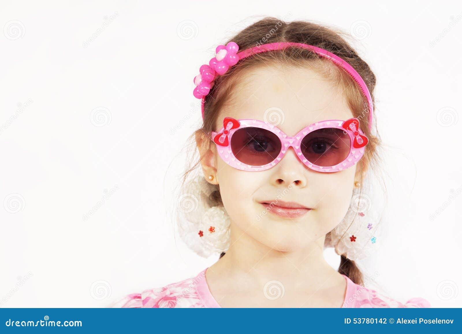 Portret dosyć śliczna młoda dziewczyna jest ubranym różowych okulary przeciwsłonecznych