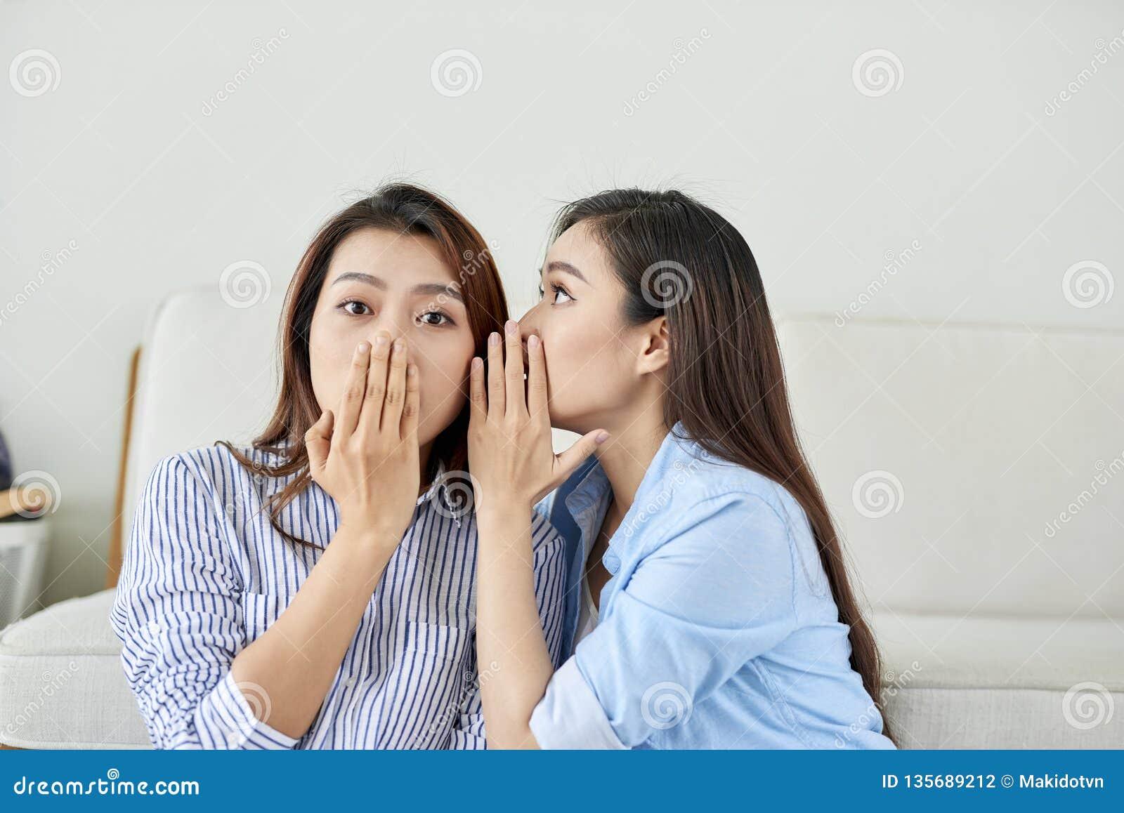 Portret dwa młodej atrakcyjnej szczęśliwej kobiety z podsłuchuje szepty tajna tajemnica w studiu na żywym pokoju _