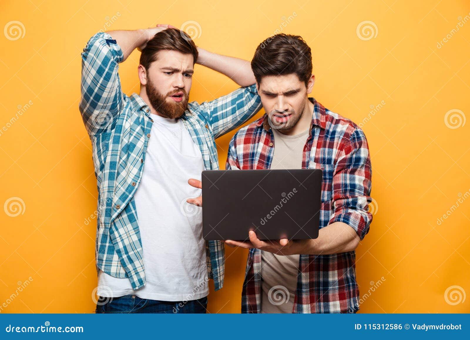 Portret dwa wzburzonego młodego człowieka używa laptop