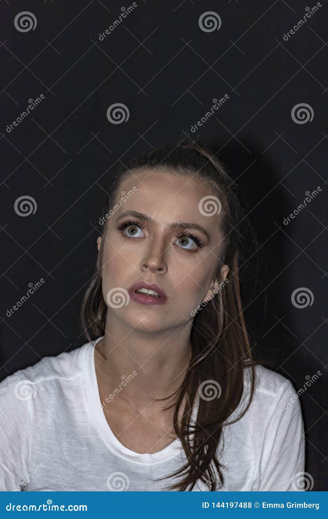 Portret dziewczyna patrzeje oddolny z długie włosy i zielonymi oczami w białej koszulce Czarny t?o