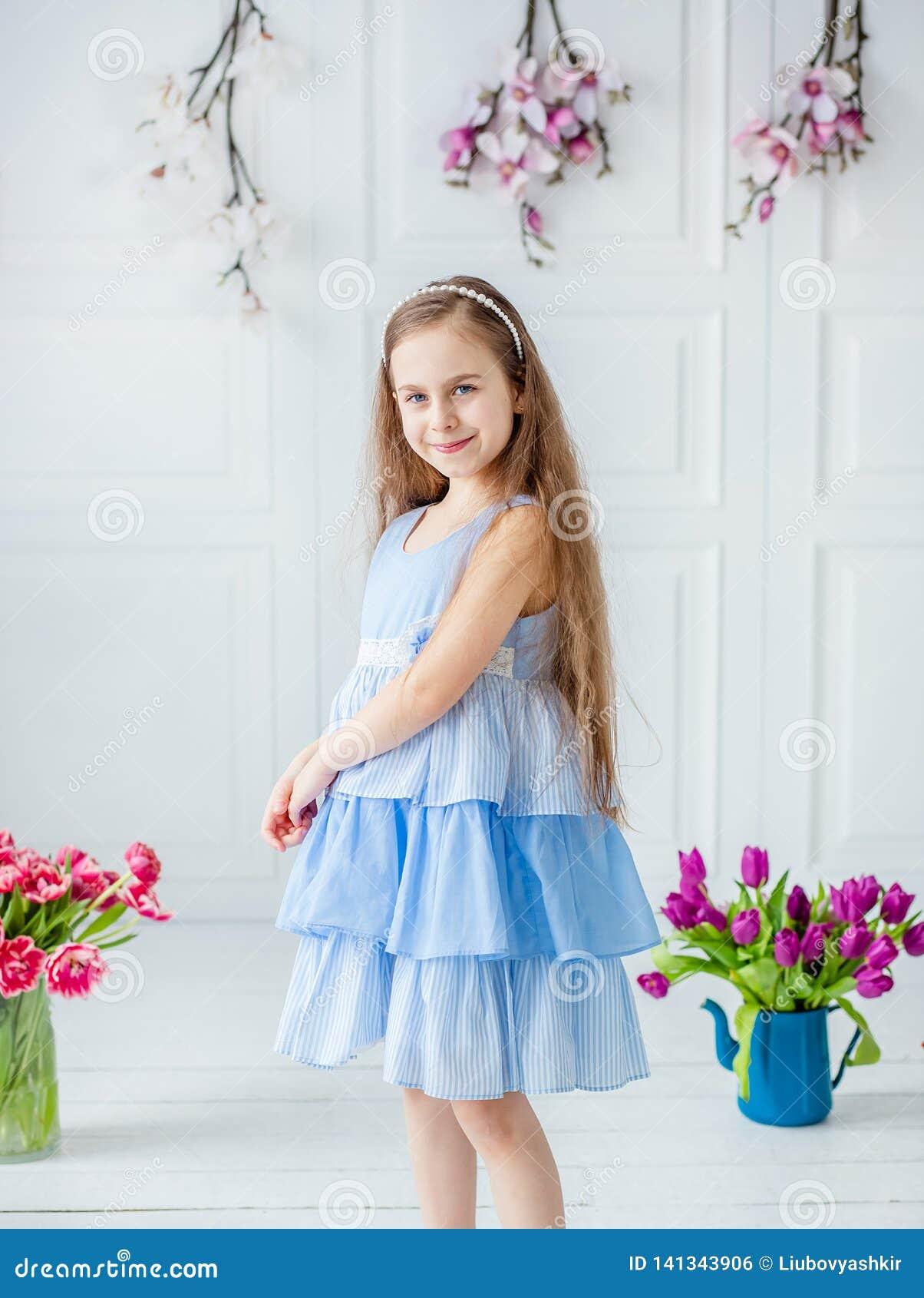 Portret dziewczyna wśród wiosny piękna błękitnooka dziewczyna, troszkę kwitnie w jaskrawym pokoju